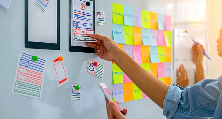working on a white board with notes to improve the user flow and the experience