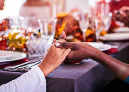 people holding hands during Thanksgiving dinner