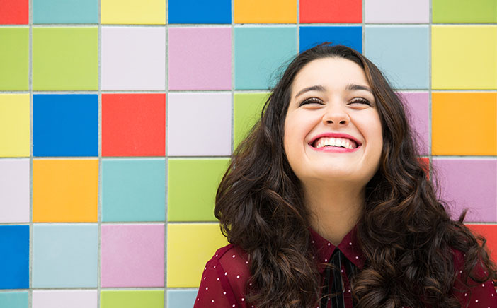Woman with a big smile standing in front of a multicolor patterned wall