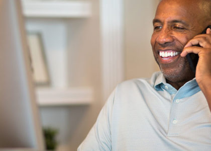 Black man on the phone and smiling at his computer monitor